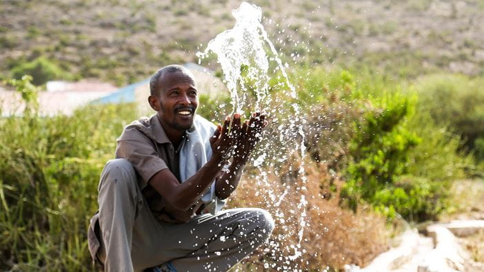 A man splashes water at a newly built water point in Somalia
