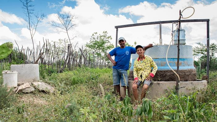 Farmers in north east Brazil pose with their biodigestor which turns waste into gas for cooking.