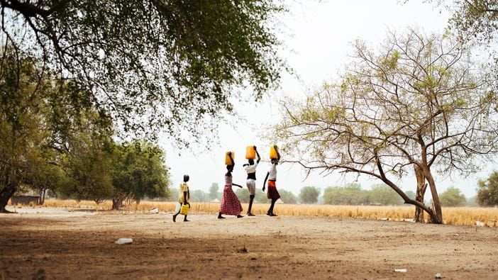 Women return home with water after visiting a borehole in South Sudan.