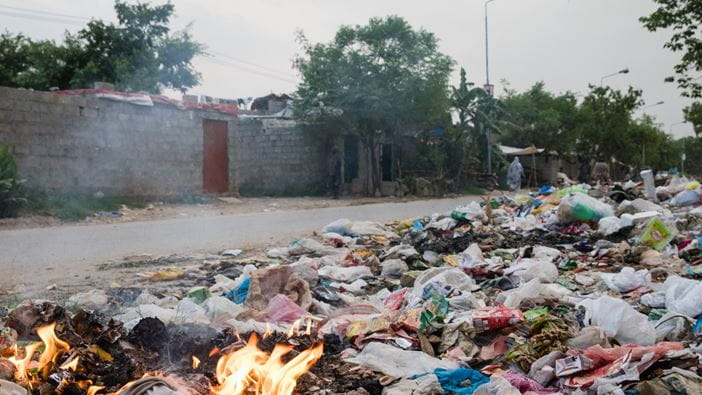 Rubbish burning on the side of the road in an informal settlement in Pakistan.