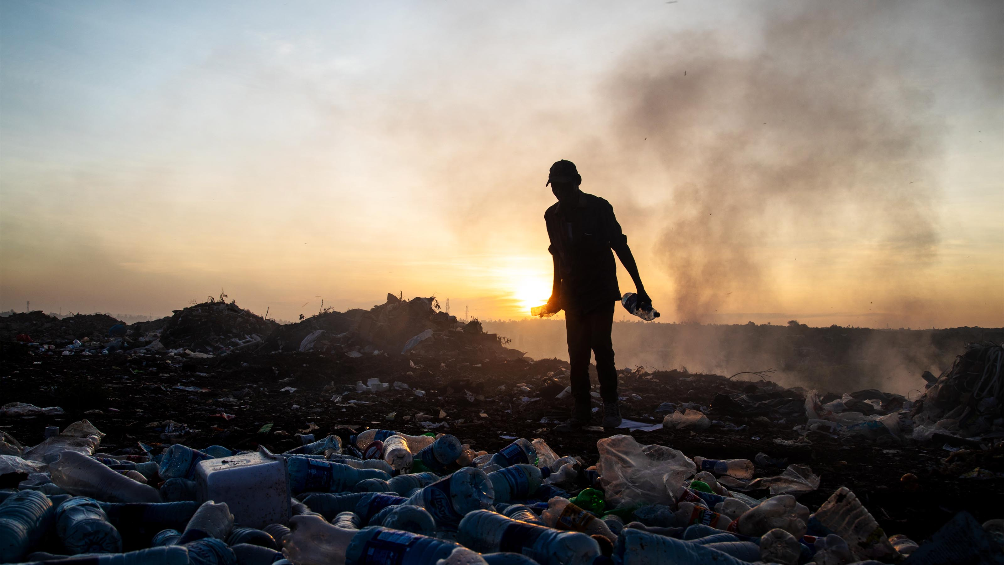 A waste picker collecting plastic bottles at a dump in Tanzania.