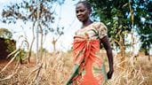 A woman walks through a field near her village in Tanzania