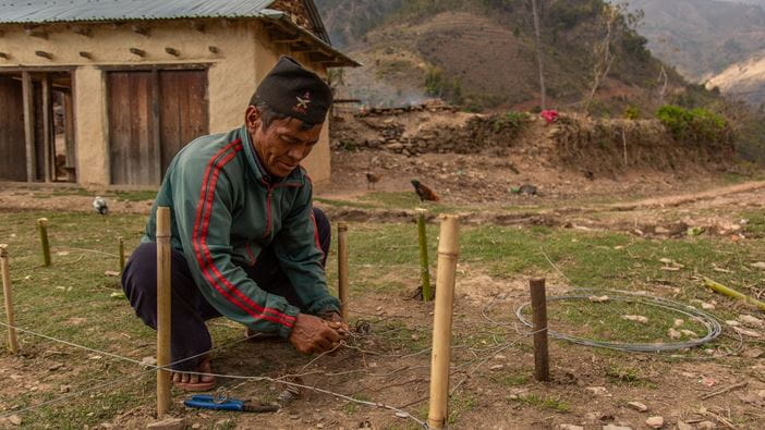 A man making a Gabion to stop landslides in a Village in Nepal