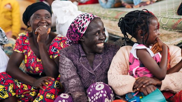 Internally displaced people in Nigeria gather for a presentation on WASH