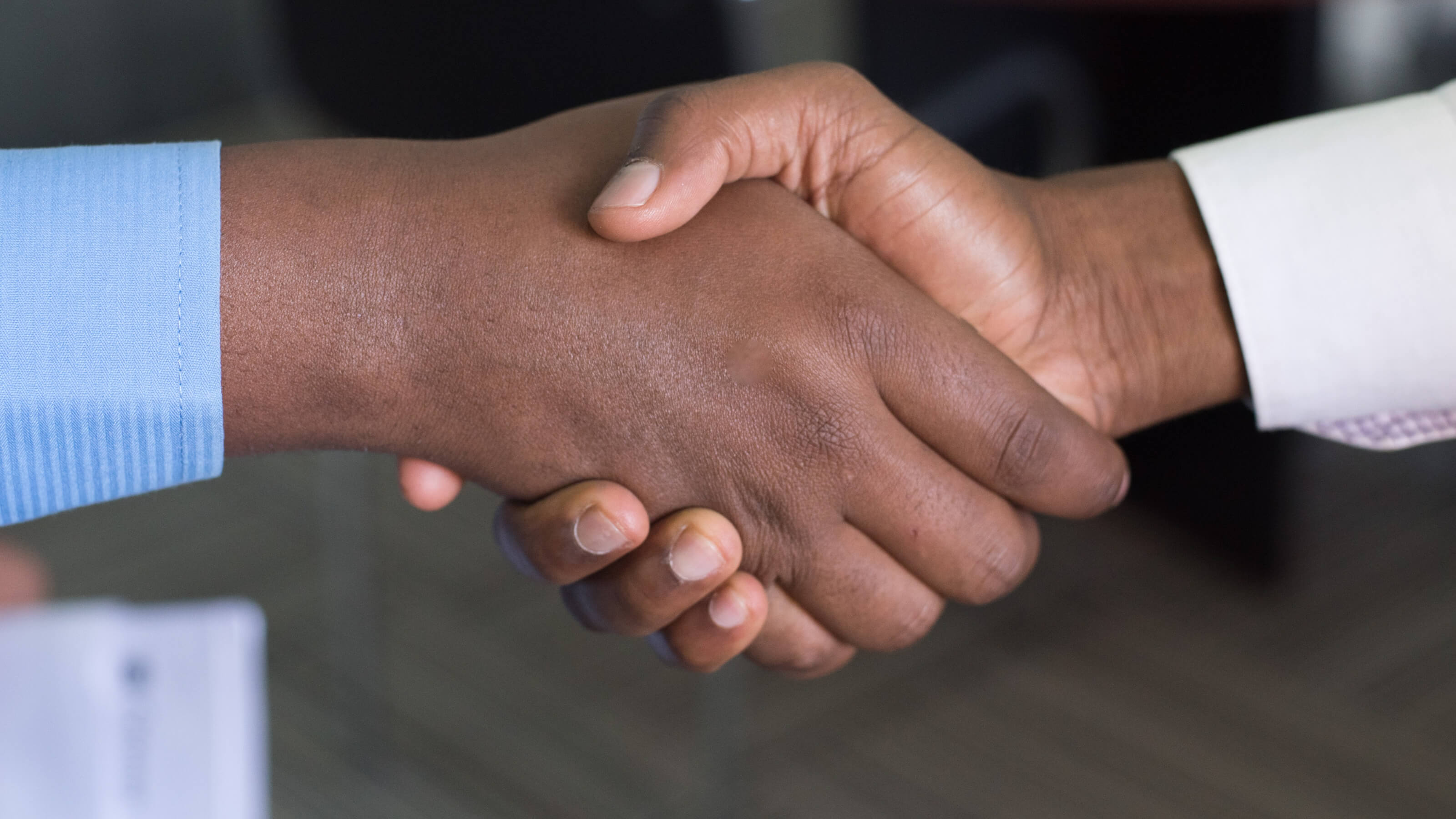 Two people shake hands as a sign of peace and reconciliation