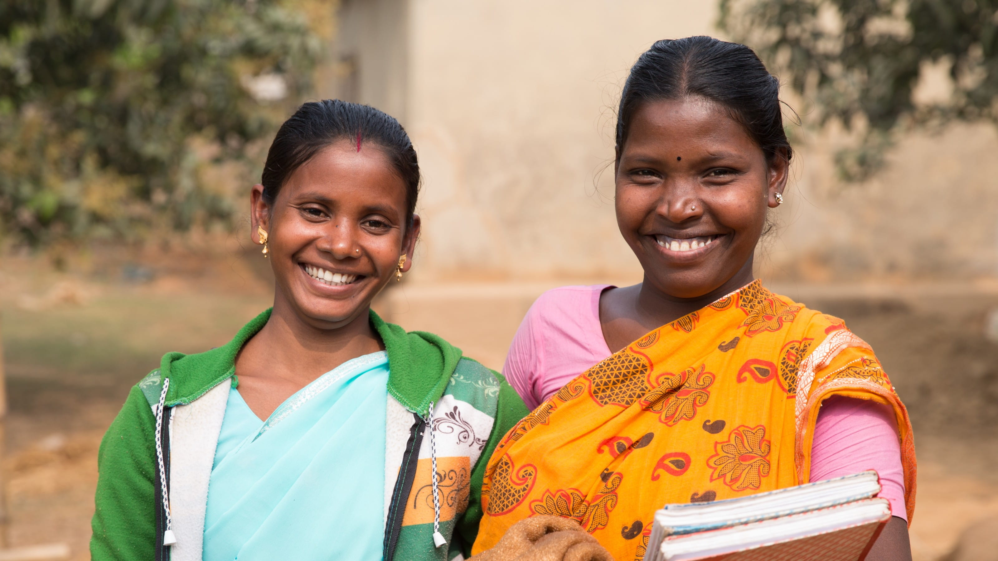 Two women invest in their local community through a savings and loans group in Bangladesh
