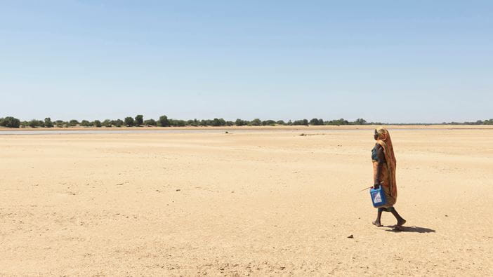 Woman walking across a naked river bed in search of water in Chad