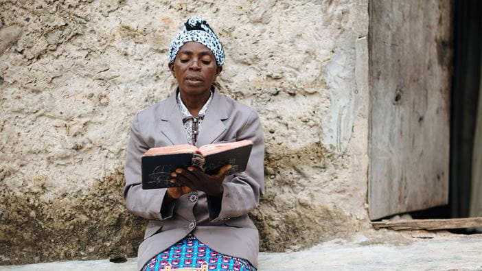A woman from Angola reads her bible at home