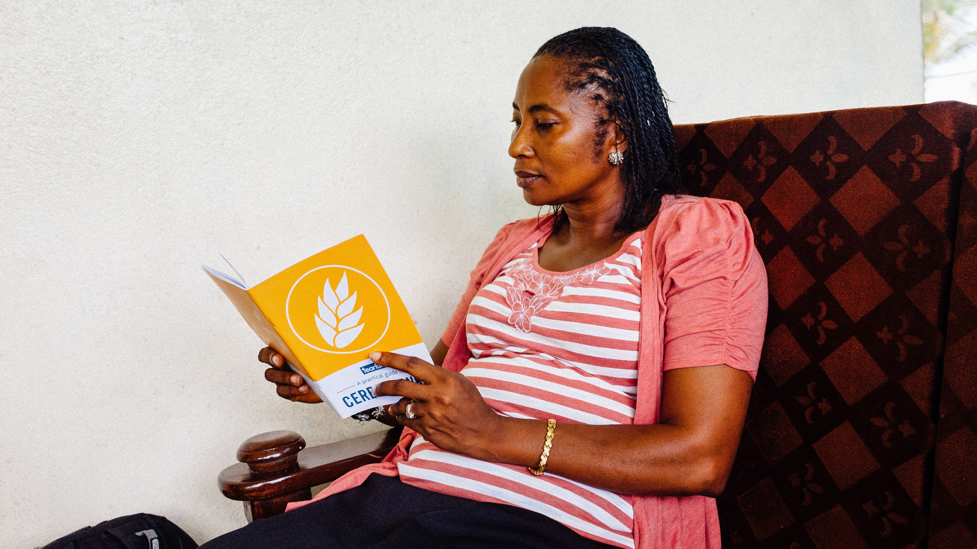 "Woman reading Tearfund booklet ""A practical guide to cereal banks"". Photo: Andrew Philip/Tearfund"